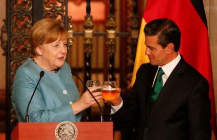 Germany's Chancellor Angela Merkel makes a toast with Mexico's President Enrique Pena Nieto before dinner at National Palace in Mexico City